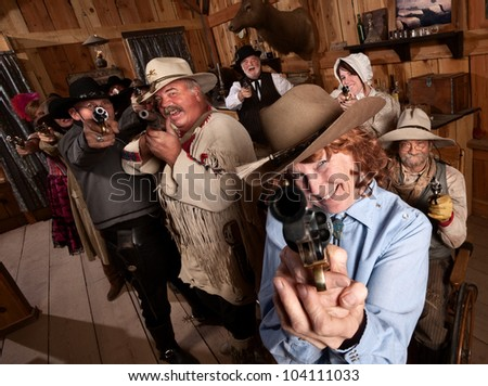 Pretty elderly lady with pistol in old saloon - stock photo