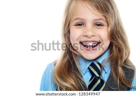 Pretty elementary school girl posing cheerfully. Closeup shot. - stock photo