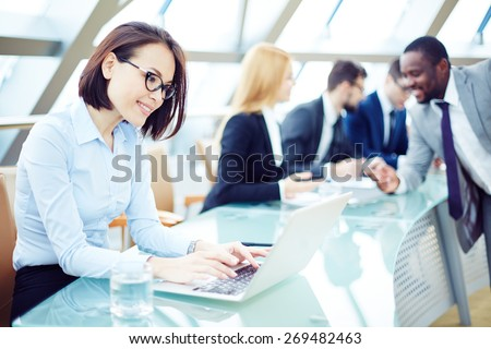 Pretty employee typing on laptop in working environment - stock photo