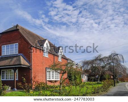 pretty english cottage in a village - stock photo