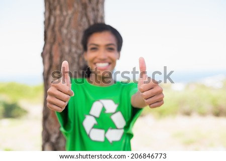 Pretty environmental activist smiling at camera showing thumbs up on a sunny day in the countryside - stock photo