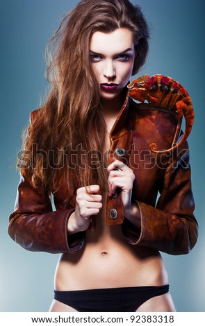 pretty erotic devil woman in leather jacket with chameleon - stock photo