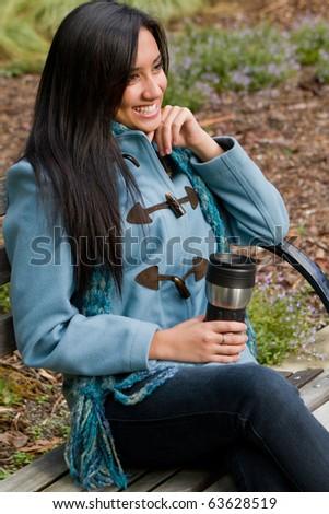 Pretty ethnic girl enjoying her coffee. - stock photo