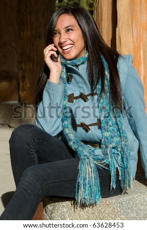 Pretty ethnic girl talking on her cellphone. - stock photo