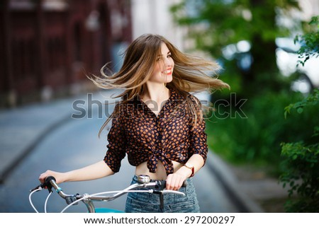 Pretty fair-haired girl is standing at the street on blouse and shorts with bicycle and having fun - stock photo