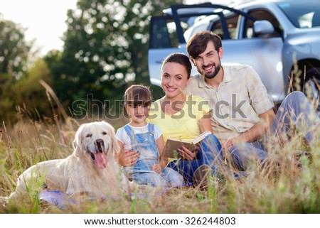 Pretty family is making journey in the nature. They are sitting on grass near car and smiling. The mother and father are embracing their daughter. The dog is lying near them - stock photo