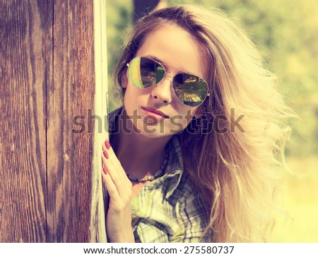 Pretty Fashion Hipster Girl in Glasses Peeking. Summer Modern Youth Lifestyle. Toned Vintage Style Photo. - stock photo