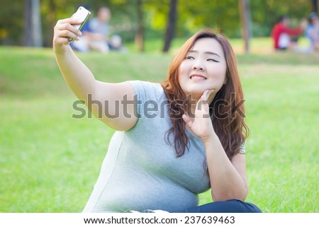 Pretty fat female takes travel selfie at the park - stock photo