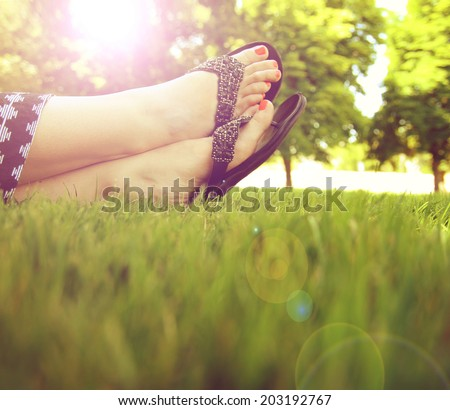 pretty feet on grass at sunset with nails painted and sandals on - stock photo