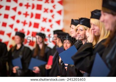 Pretty female college graduate at graduation with classmates, holding their degres. looking happy about their accomplishment - stock photo