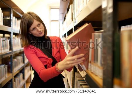 pretty female college student in a llibrary - stock photo