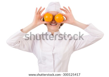 Pretty female doctor holding orange isolated on white - stock photo