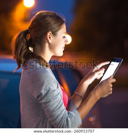 Pretty, female driver using her tablet computer (shallow DOF; color toned image) - stock photo