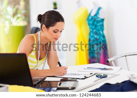 pretty female fashion designer drawing new designs - stock photo