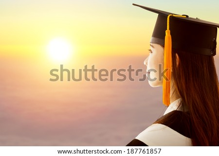pretty female graduation is thinking future with sunset background - stock photo