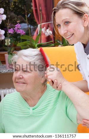 pretty female Nurse combs the hair of a senior citizen - stock photo