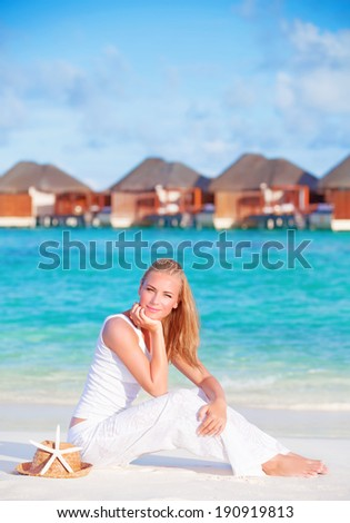 Pretty female on luxury beach resort, sitting on white clean sand and with closed eyes enjoying sunny day, summer vacation concept - stock photo