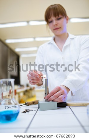 pretty female researcher/chemistry student lighting up a burner in a lab (color toned image) - stock photo