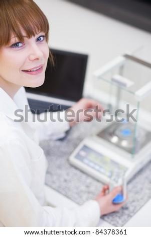 pretty female researcher using a microscope in a lab - stock photo
