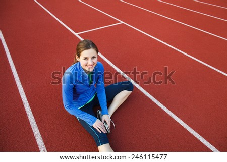 Pretty female runner stretching before her run at a track and field stadium - stock photo