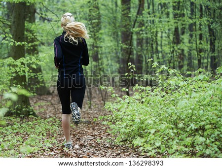 Pretty female running in the forest on side of a big City - stock photo