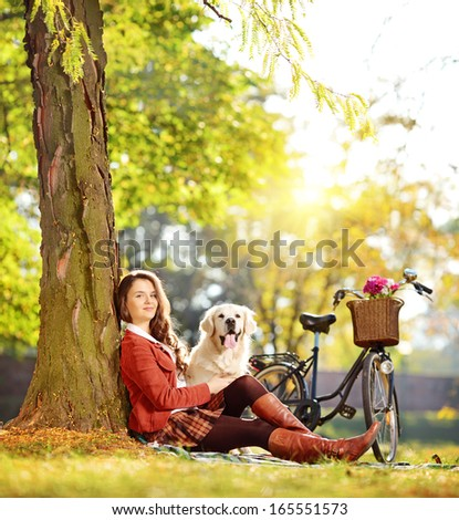 Pretty female sitting down with her labrador retriever dog in a park and looking at camera, shot with a tilt and shift lens - stock photo