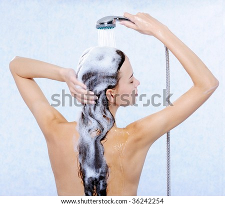 Pretty female standing back and washing her long hair - stock photo