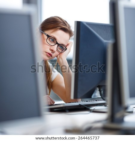 Pretty, female student looking at a desktop computer screen, learning unpleasant news about her exam results. University/office/school concept - stock photo