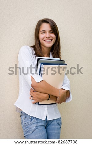 Pretty female student standing against a wall with books in her hands - stock photo