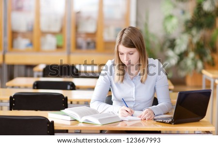 pretty female student with laptop and books working in a high school library - stock photo