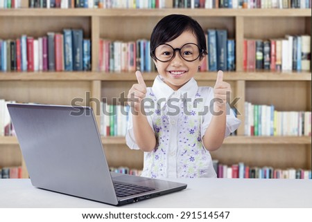 Pretty female student with laptop computer on the desk, smiling and showing thumbs up on the camera in the library - stock photo