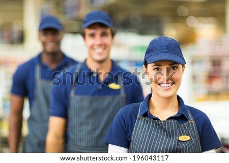 pretty female supermarket worker and team - stock photo