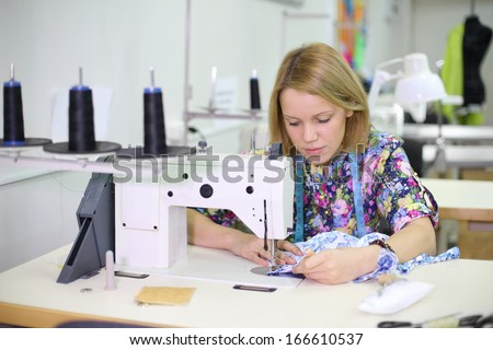 Pretty female tailor sits at table with sewing machine and sews fabric. - stock photo