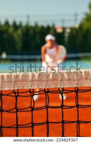 Pretty Female Tennis Player Holding A Racket and Playing a Match. Focus Is On Tennis Net - stock photo