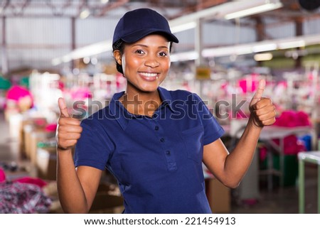 pretty female textile worker with thumbs up - stock photo