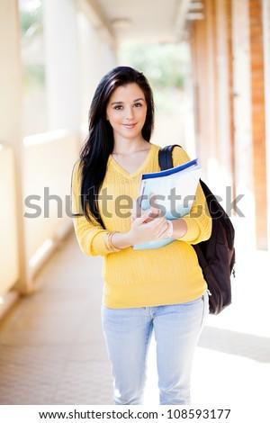 pretty female university student walking down school corridor - stock photo