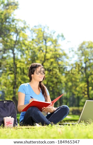 Pretty female writing in a notebook in park - stock photo