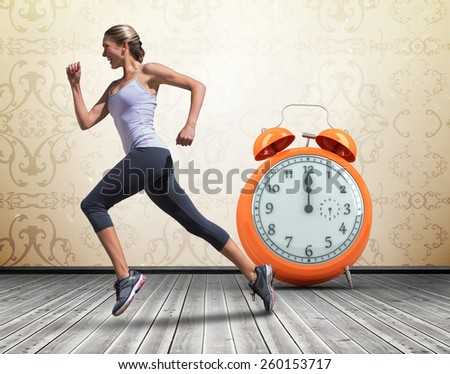 Pretty fit blonde jogging against room with wallpaper - stock photo
