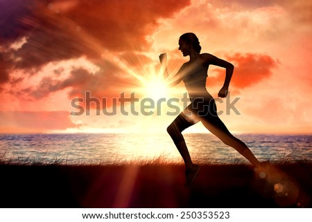 Pretty fit blonde jogging against sunrise over magical sea - stock photo
