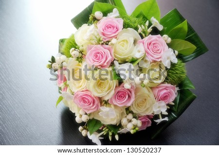 Pretty fresh pink and white bridal bouquet with roses on a bed of foliage and leaves - stock photo