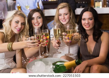 Pretty friends drinking champagne together at the bar - stock photo