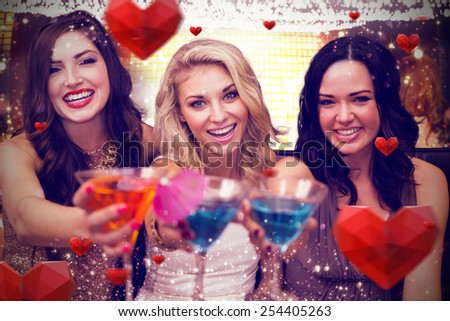 Pretty friends drinking cocktails together against hearts - stock photo