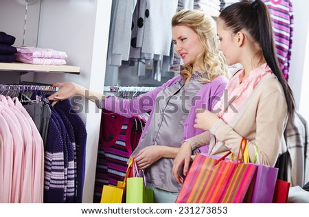 Pretty friends looking through new collection of clothes in department store - stock photo
