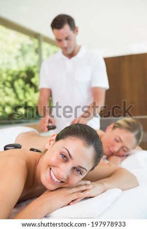 Pretty friends lying on massage tables getting hot stone massages in the health spa - stock photo