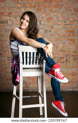 Pretty funny teenage girl wearing casual street style clothes, sitting on a bar chair, smiling, looking at camera. Against brick wall background in studio - stock photo