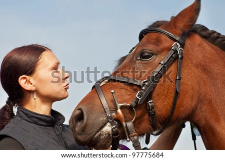 Pretty girl and bay horse during the sunny day. - stock photo