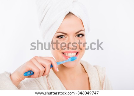 Pretty girl brushes her teeth on a white background - stock photo