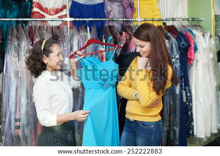 pretty girl chooses evening dress at clothing boutique. Friendly shop consultant helps her - stock photo
