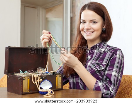 pretty girl chooses jewelry in treasure chest at home - stock photo