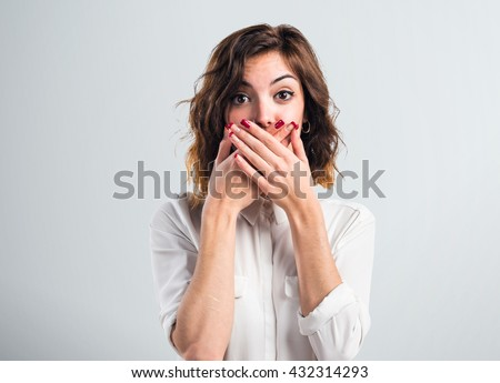 Pretty girl covering her mouth over grey background - stock photo